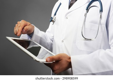 Male doctor with tablet on gray background