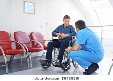Male doctor taking care of little boy in wheelchair indoors