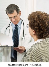 Male doctor talking with female patient. Patient is in sharp focus in the foreground with doctor blurred with background.