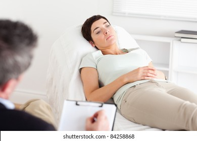 Male Doctor talking to a female patient in a room