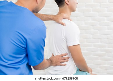 Male doctor therapist treating lower back pain patient in clinic or hospital - physical therapy concept