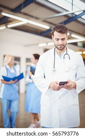 Male doctor using mobile phone at hospital