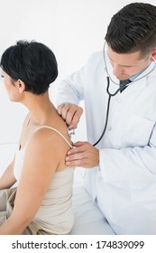 Male doctor using stethoscope on back of woman in clinic