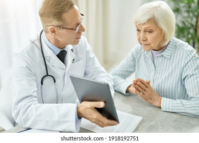 Male doctor using tablet computer while talking with old woman