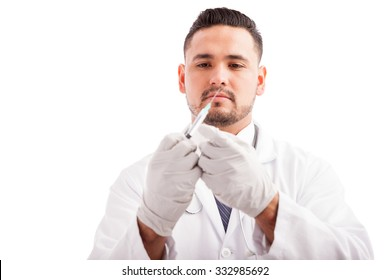 Male doctor wearing gloves and preparing a syringe against a white background