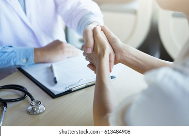 Male doctor in white coat shaking hand to female colleague. Patient filling thankful to doctor.
