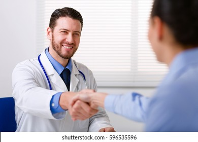 Male doctor in white coat smiling while shaking hand to female colleague blurred in foreground