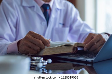 Male doctor in white lab coat reading text book, search information and working on laptop computer with  medical stethoscope on the desk in room at clinic. Medical knowledge and education concept.
