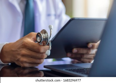 Male doctor in white lab coat, hand holding medical stethoscope and using modern digital tablet pc,  work on laptop computer at workplace. Online medical, e health or medical network concept.