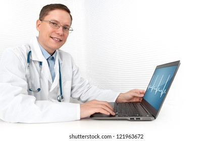 male doctor working on a laptop. heart beats cardiogram