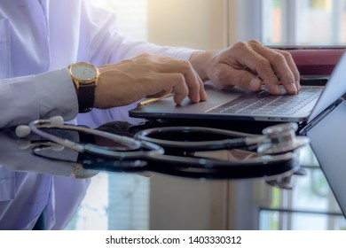 Male doctor working and typing on laptop computer with stethoscope on the desk in medical room at office. Electronics health record system(EHRs), Electronic medical record system (EMRs) concept.