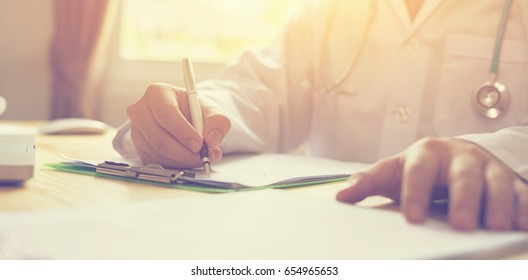 male doctor,surgeon,nurse,pharmacy with stethoscope on hospital holding clipboard,writing a prescription,Medical Exam,Healthcare and medical concept,test results,vintage color,selective focus