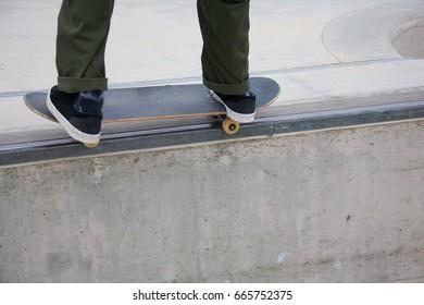 Male doing rail grind while skateboarding at Venice Skate Park in Venice Beach California.