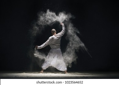 Male doing yoga in white dust cloud rearview