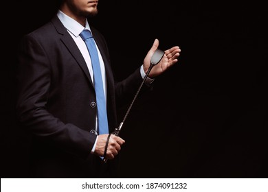 Male dominant businessman in a suit holding a leather whip Flogger for domination in BDSM sex