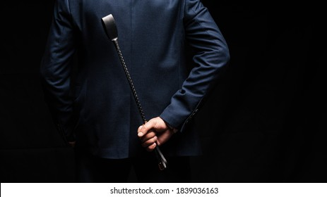 male dominant holds a leather whip Flogger for hard BDSM sex with spanking