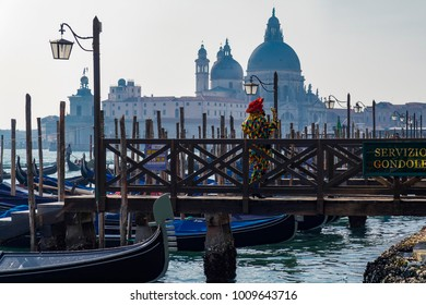 Male dressed with traditional Venetian carnival costume at Venice, Italy lagoon. Unidentified person at the gondolas service waterfront with moored empty gondolas.