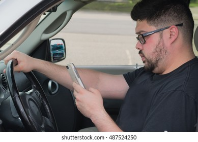 Male driver being distracted by a cell phone text instead of watching the road. Police in rear view mirror.