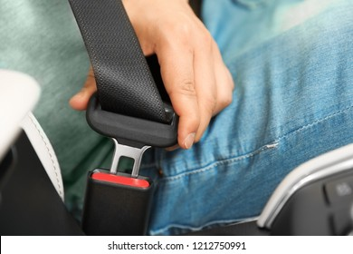 Male driver fastening safety belt in car, closeup
