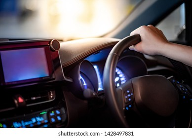 Male driver hand holding on steering wheel using digital dashboard monitor for GPS navigation on the car console in modern car. Urban driving lifestyle with automobile technology