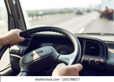 Male driver hands are holding steering wheel of truck during the movement in the road. Image with selective focus on the wheel, dashboard and blurred windshield