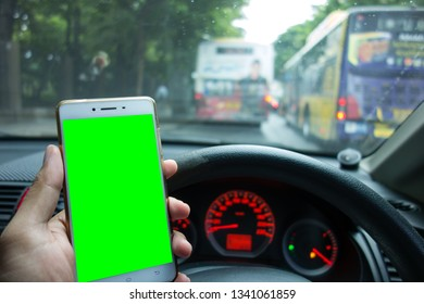 Male driver holding white mobile smart phone on the green screen with blurred traffic jam and empty fuel in background