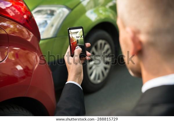Männlicher Fahrer fotografiert mit seinem Handy nach Verkehrskollision