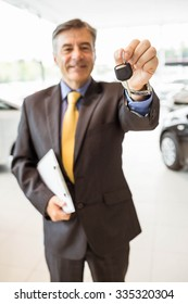 Male driver showing a key after buying a new car at new car showroom