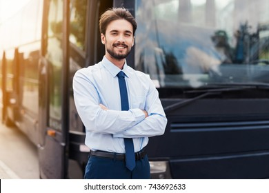 A male driver smiling and posing against a black tourist bus. Behind the back is a modern black tourist bus. On the man the driver's uniform.