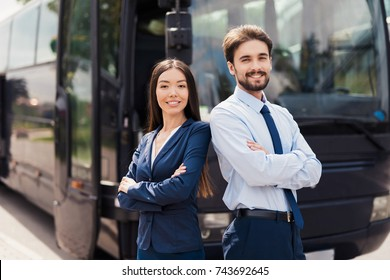 A male driver is smiling and posing with a woman stewardess. Behind them stands a modern black tourist bus. On the man and the woman there is a special uniform.
