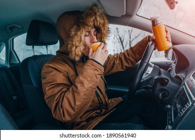 A male driver warms up with a hot drink from a thermos while his car stalled somewhere in the winter mountains