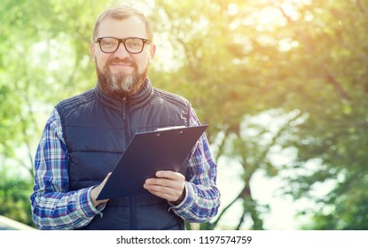 Male ecologist takes notes on the background of green plants.