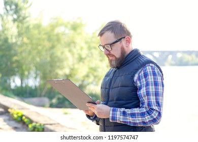 Male ecologist writes information about environmental problems. Ecological control of a condition of a reservoir and environment.