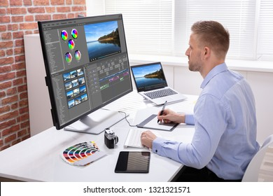 Male Editor Editing Video On Computer Over Wooden Desk