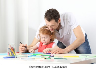 A male educator or a vather doing painting together