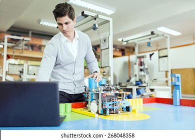 Male electrical engineer programming a robot during robotics class
