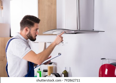 Male Electrician With Clipboard Repairing Kitchen Extractor Filter