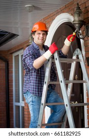 Male electrician in hardhat standing stepladder and repairing lamp on house