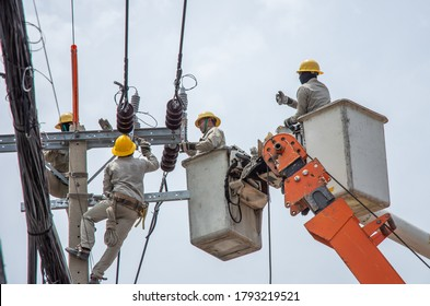 A male electrician officer climbs a pole and uses a cable car to maintain a high voltage line system on a dangerous electric pole in Nonthaburi province. Thailand Date 06-08-2020