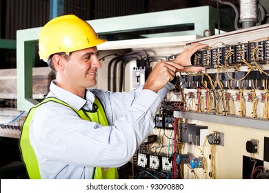 male electrician repairing industrial machine control component