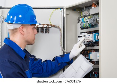 Male Electrician Testing Fusebox With Blueprint In Hand