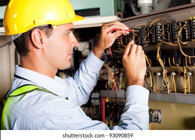 male electrician testing industrial machine