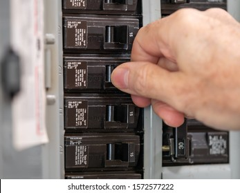 Male electrician turning off power for electrical outlet at circuit breaker box. Resetting tripped breaker in residential electricity power panel.