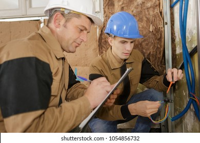 male electricians looking at cables and making notes on clipboard
