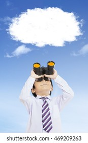 Male elementary school student looking at the empty speech bubble with a binoculars, shot outdoors