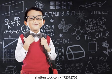 Male elementary school student standing in the class while wearing uniform and carry bag with doodles on chalkboard