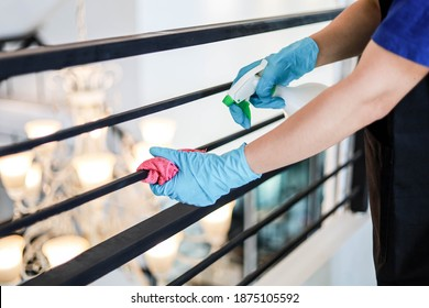 A male employee cleaning the restaurant's second floor balcony handrail, cleaning to prevent the transmission of COVID-19, COVID-19 prevention concept.