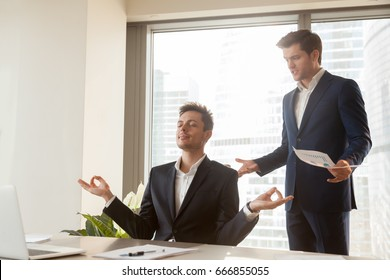 Male employee meditating at workplace sitting in yoga pose with eyes closed, not listening to screaming boss, blaming for laziness, work undone and missing deadline, no stress management, keep calm