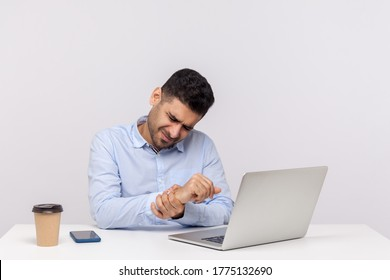 Male employee sitting office workplace with laptop, massaging sore wrist, suffering pinched nerve, stiff muscles, carpal tunnel syndrome after typing on computer. indoor studio shot, white background