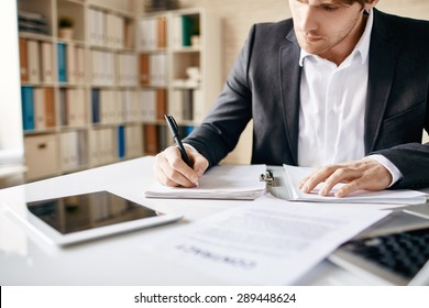Male employee writing business plan at workplace